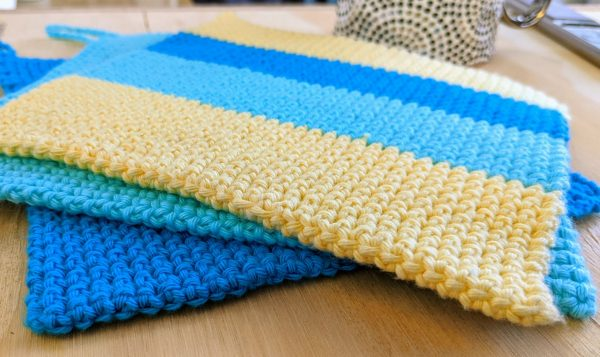 three crochet potholders on the table