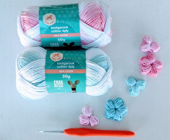 deux écheveaux de laine, un crochet et cinq fleurs au crochet