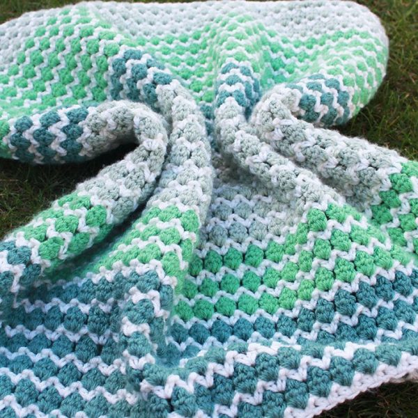 green, white and blue coloured blanket