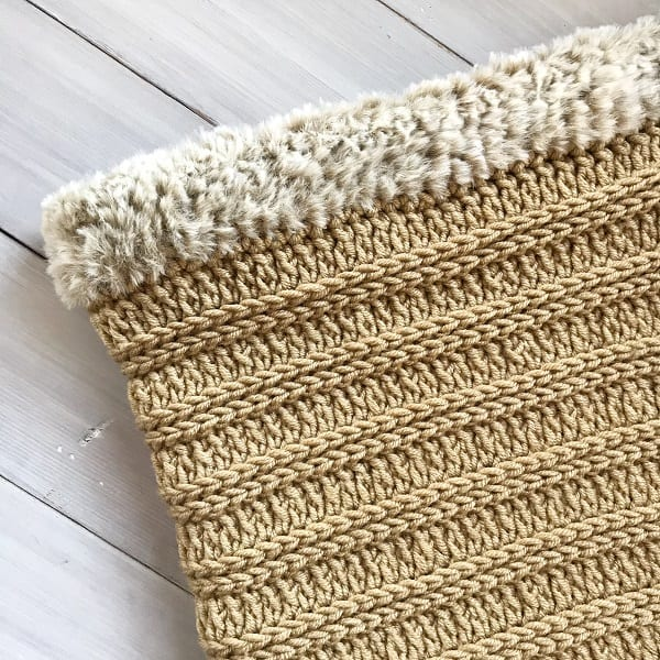beige coloured crocheted blanket with a furry border