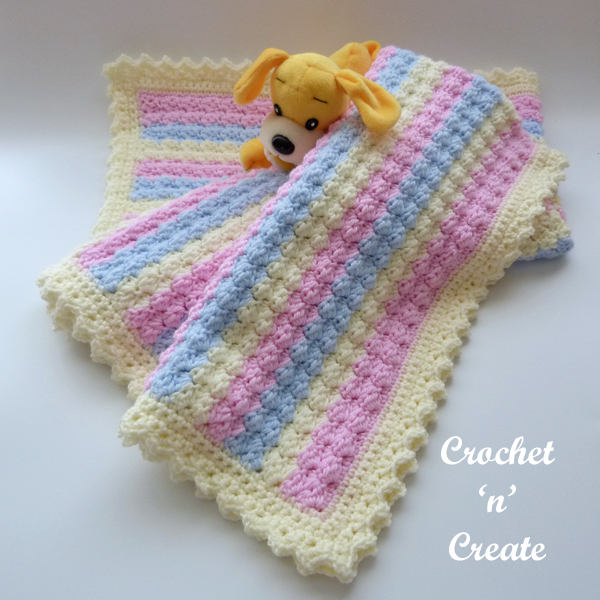 crochet baby blanket in pastel colours with a toy dog