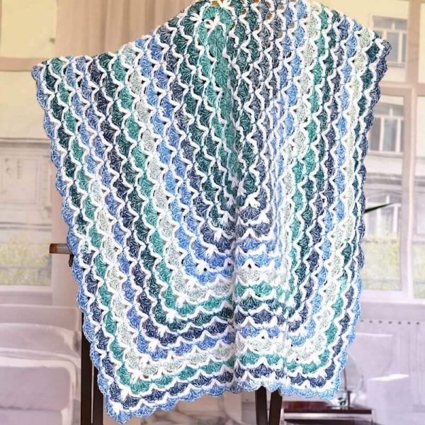 blue and white crocheted blanket in shell pattern hanging over the chair
