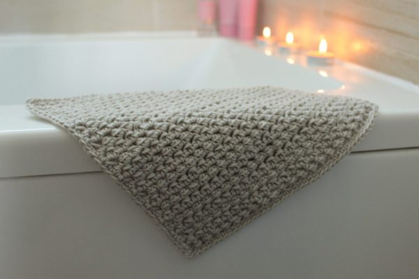 crochet washcloth on top of bath tub, candles in the background