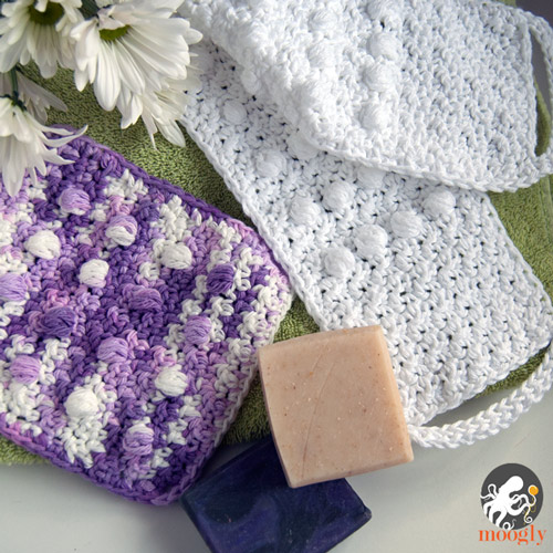 purple and white crochet washcloths with soap and flowers