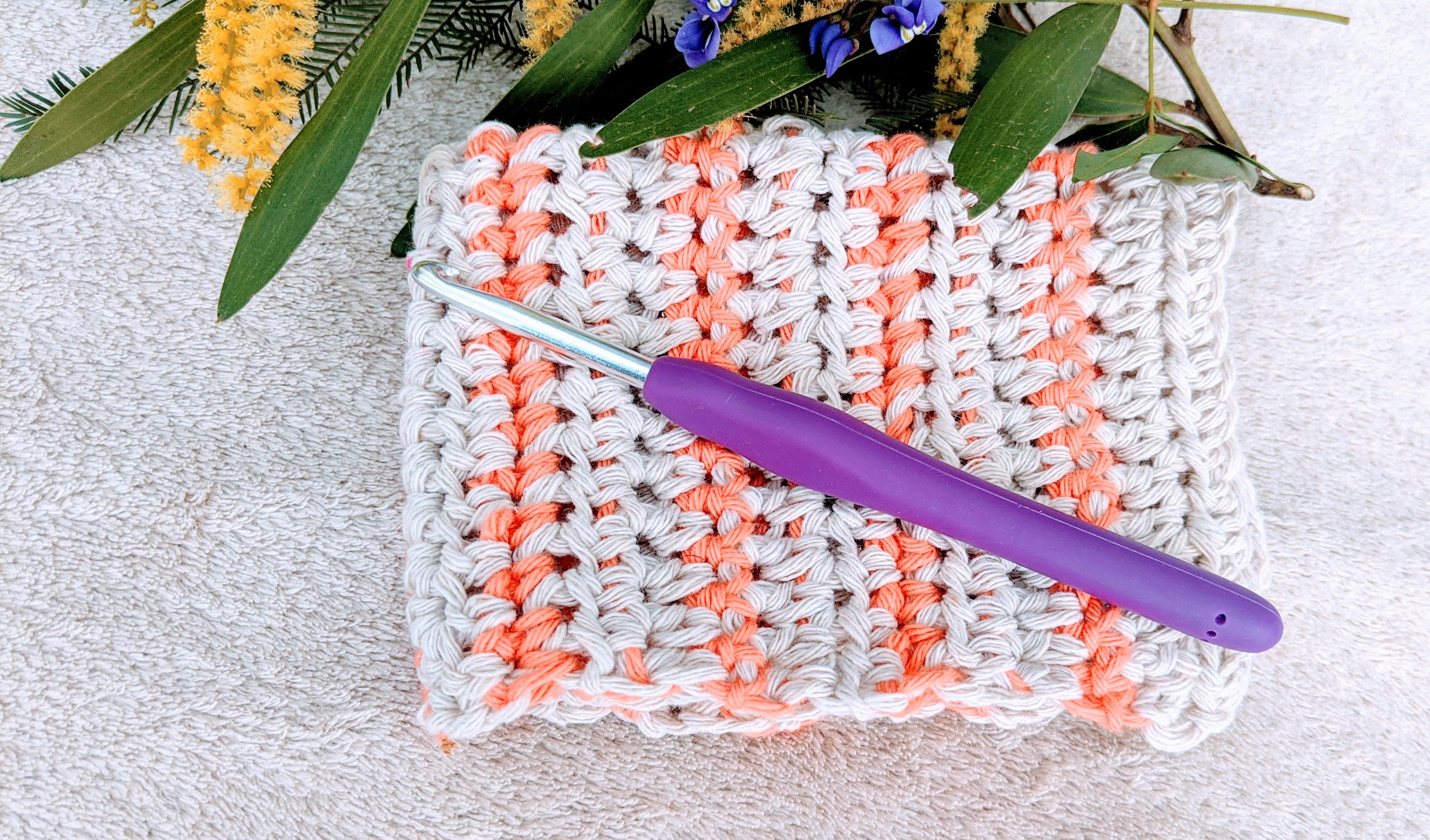 gant de toilette au crochet à rayures orange et blanc cassé, avec un crochet violet et des fleurs en arrière-plan