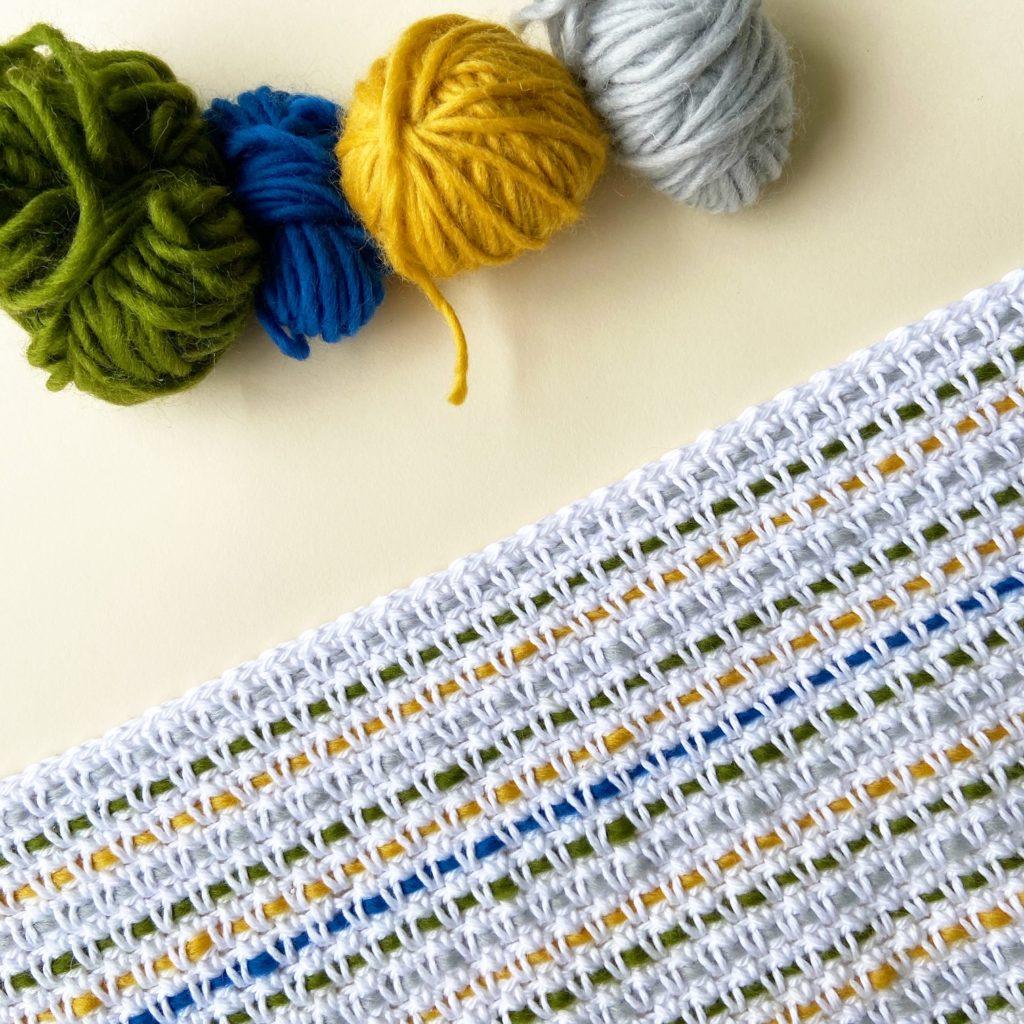 couverture au crochet avec 4 pelotes de laine de différentes couleurs